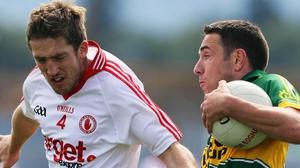 Kerry's Declan O'Sullivan (r) sidesteps Tyrone corner-back Dermot Carlin