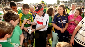 The ever-gracious Tyrone boss Mickey Harte signs autographs for Kerry fans after the game