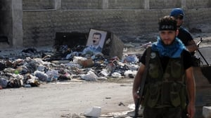 Opposition fighters guard a checkpoint during clashes with forces loyal to Mr Assad in Aleppo