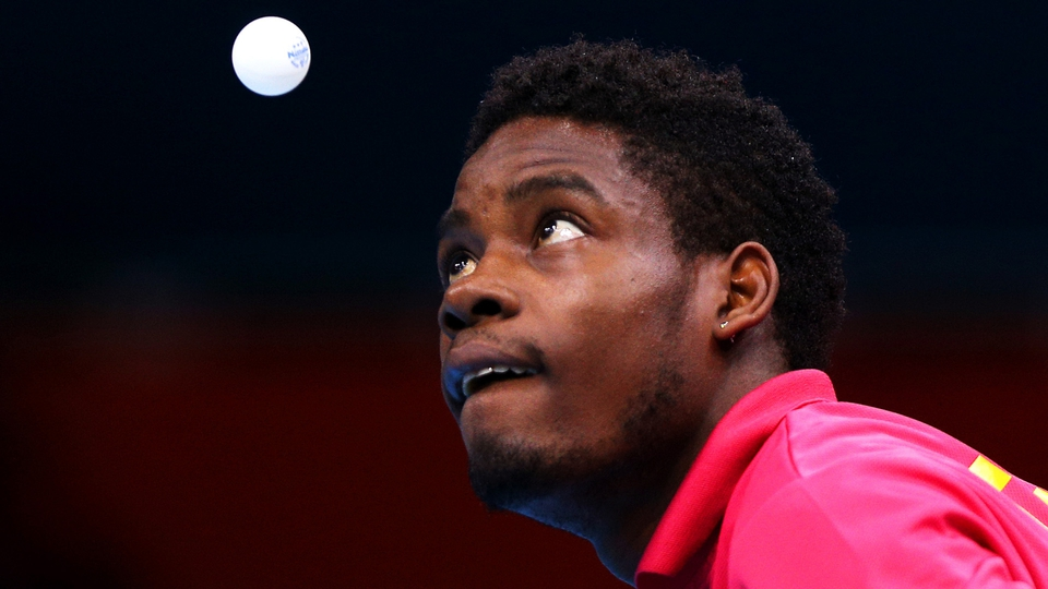 Mawussi Agbetoglo of Togo serves against Justin Han of Australia during their men's singles preliminary round match
