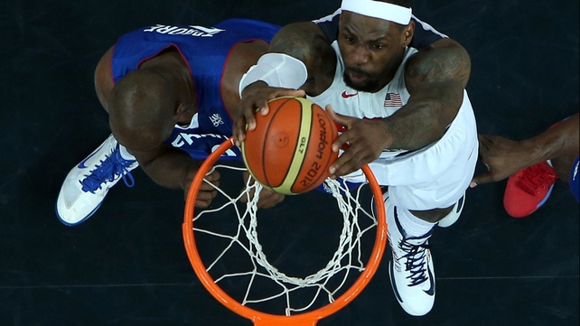 LeBron James scores despite the attention of France's Ali Traore