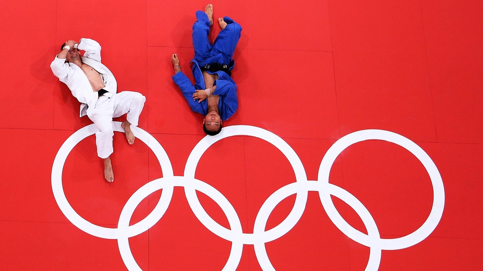 Pawel Zagrodnik of Poland and Masashi Ebinuma of Japan lie on the mat after their match in the Men's 66kg Judo