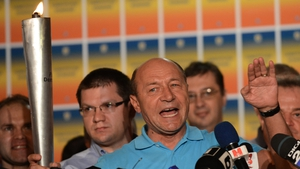 Romanian President Traian Basescu holds The Democracy Torch as he addresses reporters