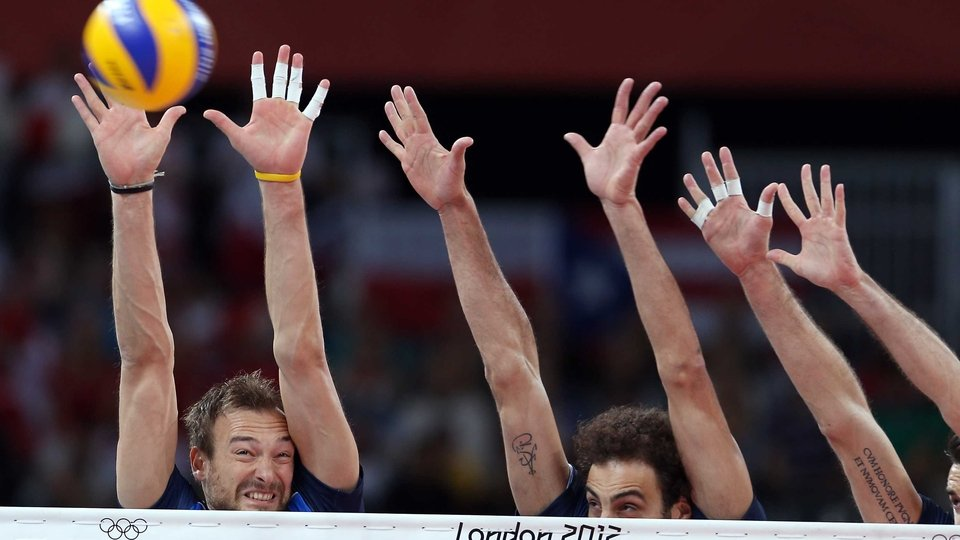 Michal Lasko and Alessandro Fei of Italy try to stop a shot by Poland