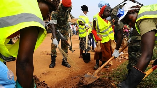 Ugandan Military Police officers help in collecting garbage at Makindye Division, a Kampala suburb during a cleaning exercise