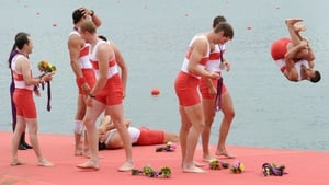 A Canadian team member jumps into the water as his team-mates celebrate winning silver in the Men's Eight Final in Rowing