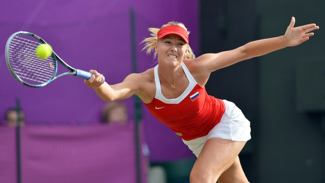 Maria Sharapova grimaces as she returns a Sabine Lisicki serve