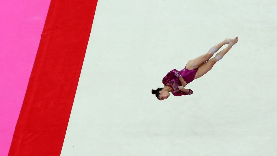 Alexandra Raisman is airborne during the floor exercise in the Artistic Gymnastics Women's Individual All-Around final