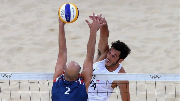 Phil Dalhausser of the United States blocks the shot of Italy's Paolo Nicolai