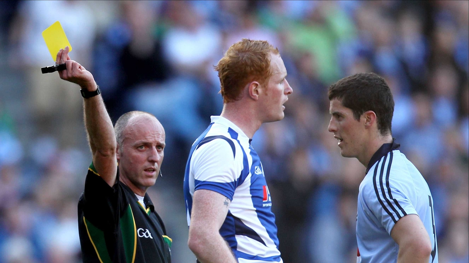 Dublin's Rory O'Carroll (r) and Laois' Padraig Clancy are booked by referee Cormac Reilly