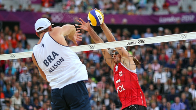 Alison Cerutti of Brazil hits a return against against Poland's Mariusz Prudel