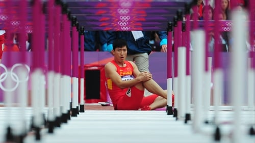 Xiang Liu of China sits on the track after getting injured