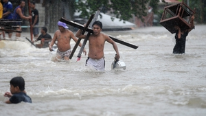 Residents carry their belongings as they wade through flood waters after a river overflowed following torrential rain in Manila