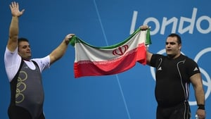 Behdad Salimikordasiabi (R) of Iran celebrates winning the gold medal with compatriot Sajjad Anoushiravani Hamlabad