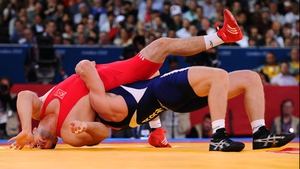 Cenk Ildem of Turkey (red) competes with Artur Aleksanyan of Armenia in wrestling