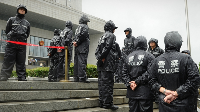Police stand guard the outside the Intermediate People's Court in Hefei