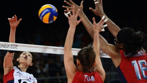 South Korea's Kim Yeon-Koung (L) spikes as Logan Tom (C) and Foluke Akinradewo of the US attempt to block