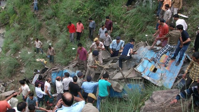 Onlookers and rescuers at the scene of a bus crash in northern India