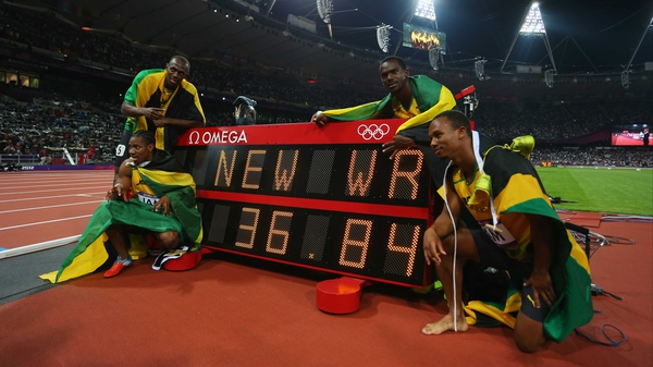 Usain Bolt, Yohan Blake, Michael Frater and Nesta Carter of Jamaica celebrate next to the clock after winning gold and setting a new world record of 36.84