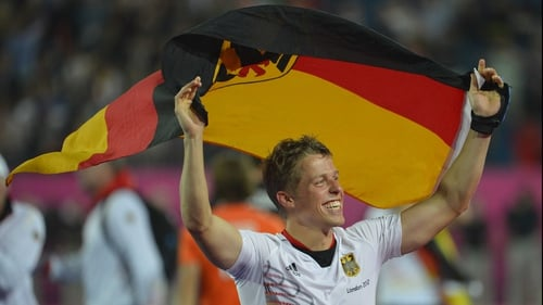 Germany's Timo Wess carries his national flag after the game