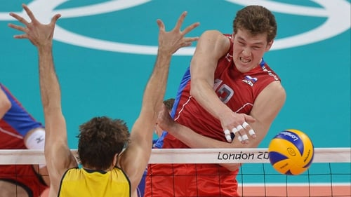Russia's Dmitriy Muserskiy spikes the ball past Brazil's Lucas Saatkamp