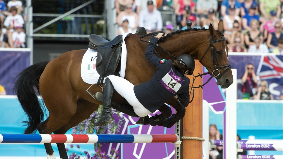 Mexico's Tamara Vega falls from her horse Douce de Roulad during the showjumping part of the women's modern pentathlon