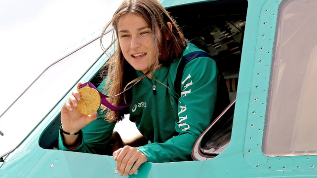 Katie Taylor showed her medal from the cockpit of the plane after it landed