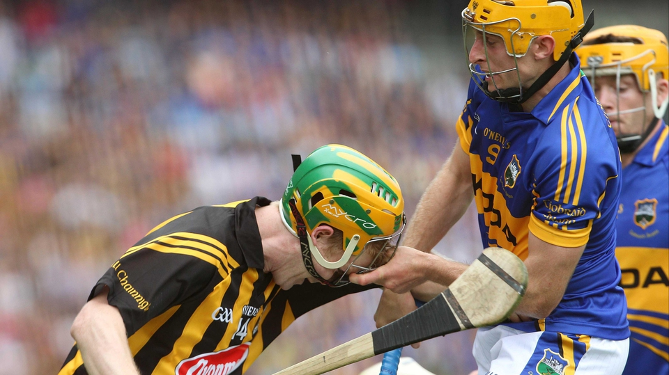 Tipperary's Shane McGrath pulls off the helmet of Richie Power of Kilkenny