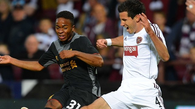 Liverpool's English midfielder Raheem Sterling (L) shoots past Hearts' Australian defender Ryan McGowan