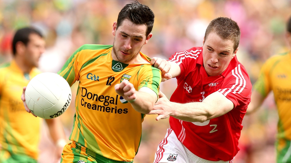Mark McHugh of Donegal shields possession from Colm O'Neill of Cork
