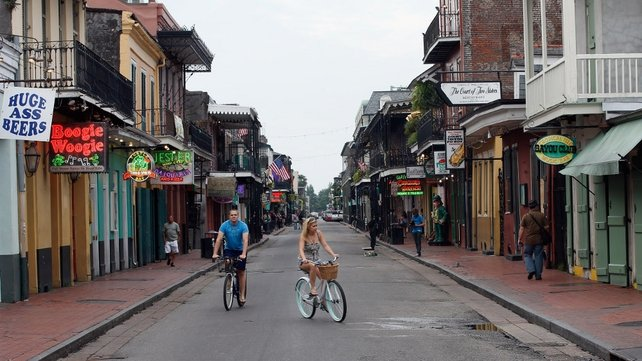 People ride bicycles down a virtually empty Bourbon street in New Orleans