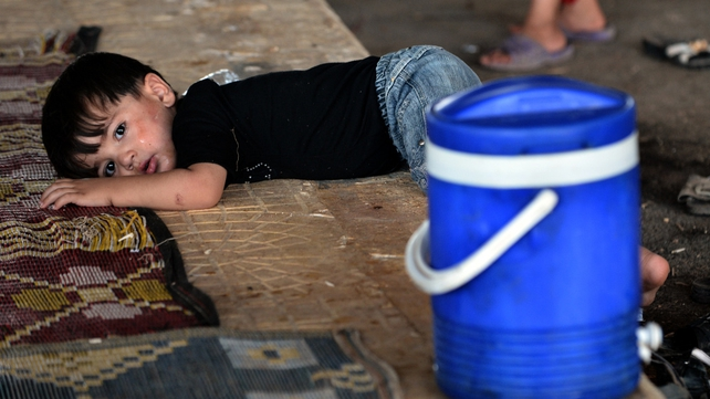 A young Syrian boy lies on the ground after his family were not allowed to enter Turkey