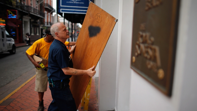 Workers place plywood on the windows of a hotel in New Orleans