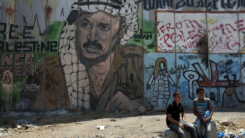 A Palestinian boys sit next to a mural of late Palestinian leader Yasser Arafat