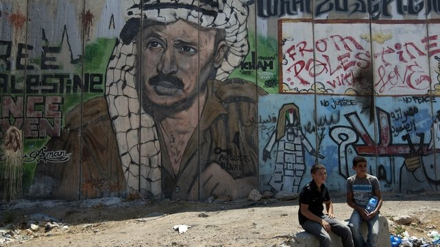 Palestinian boys sit next to a mural of late Palestinian leader Yasser Arafat