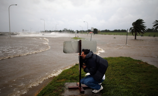 A man crouches behind a sign to avoid the high winds on the lake