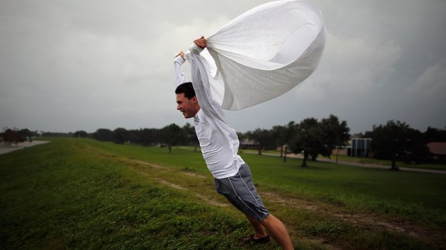 Matthew Pettus holds a sheet open in the wind on the levee near Lake Pontchatrain as Hurricane Isaac approaches