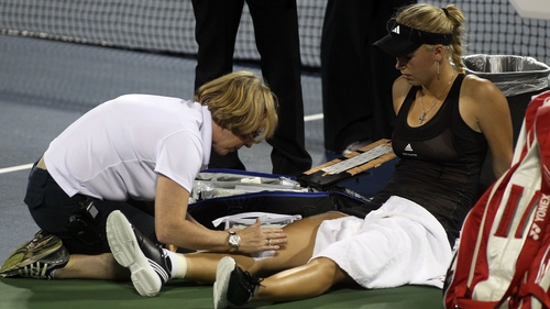 Caroline Wozniacki gets some medical attention during her opening round defeat to  Romania's Irina-Camelia Begu