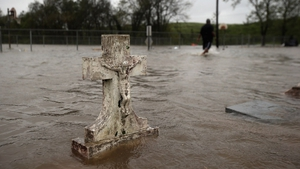 Errol Ragas walks past a flooded cemetery while recovering dry blankets from his home in Plaquemines Parish