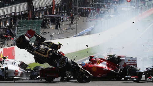 Romain Grosjean's car is catapulted into the air at the first corner in the Belgian Grand Prix