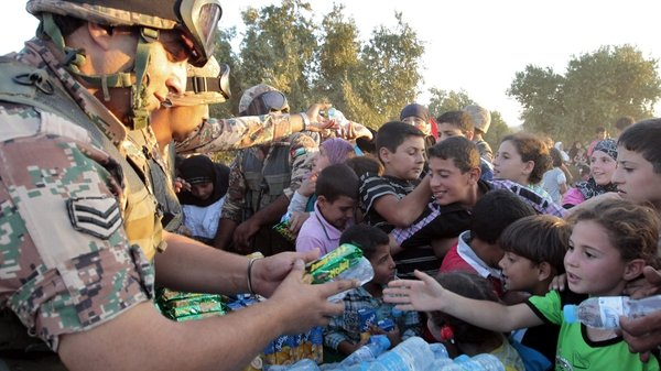 Jordanian soldiers distribute water and snacks to newly-arrived Syrian refugees after they crossed the border into Jordan
