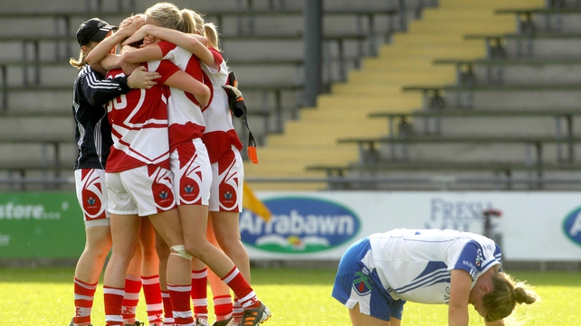 Cork players celebrate the final whistle as Ellen McCarron of Monaghan drops to the ground