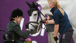 Helen Kearney pats her horse Mister Cool after winning bronze in the dressage individual freestyle test - grade Ia