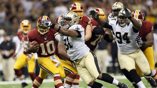Robert Griffin III escapes the attentions of Will Smith of the New Orleans Saints