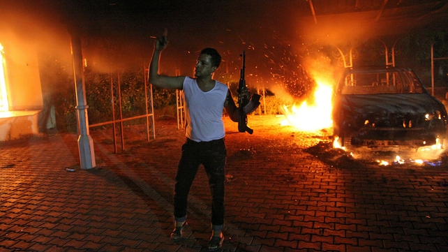 An armed man waves his rifle as buildings and cars are engulfed in flames after being set on fire inside the US consulate compound in Benghazi on Tuesday night