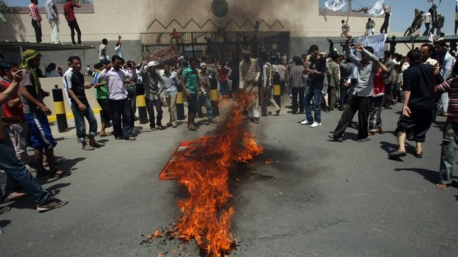 Yemeni protesters gather around a fire during a demonstration outside the US embassy in Sanaa