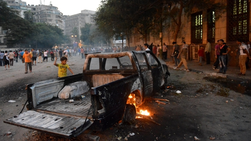 A burned-out vehicle amid a protest against the film in Cairo