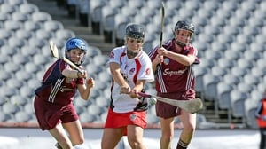 Derry's Kate McAnenly scores a goal despite the attentions of two Galway players