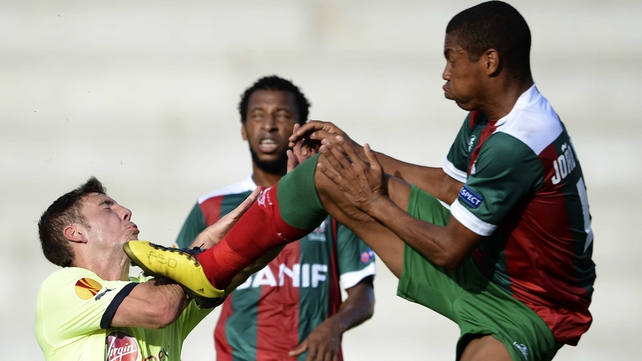 Dan Gosling (L) takes a boot to the head from Maritimo defender Joao Guilherme