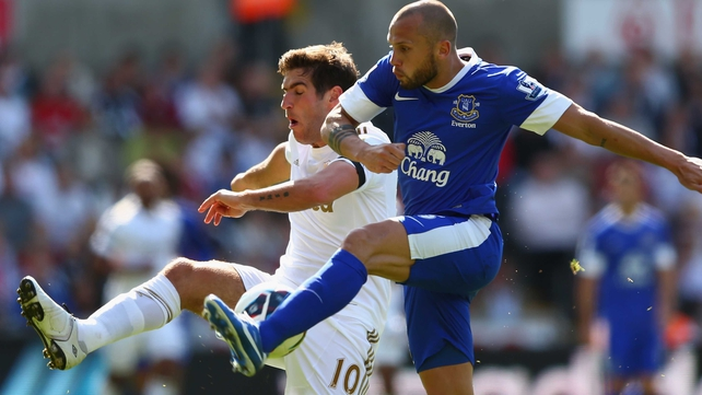 Danny Graham of Swansea City is challenged by Everton's John Heitinga